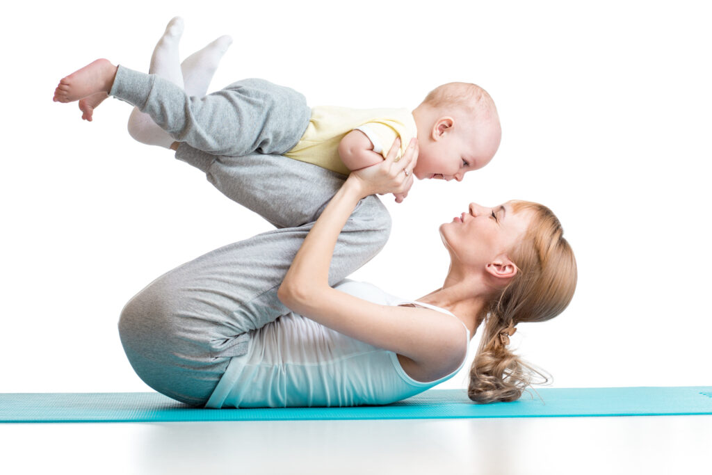 young mother does fitness exercises together with baby boy