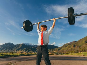 A young boy dressed as a businessman is showing his strength outside by lifting a barbell and weights. He is showing his confidence and inner strength to accomplish a difficult task amidst adversity. Image taken in Utah, USA.